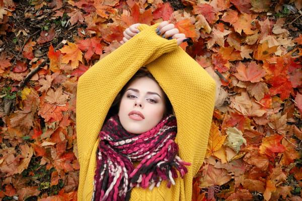 Saiba como se cuidar no inverno: mulher deitada sobre folhas coloridas de árvore.
