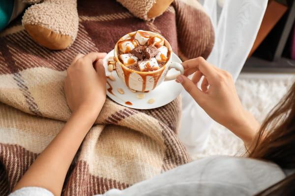 Saiba como se cuidar no inverno: mulher tomando uma xícara de café quente com desenhos personalizados.