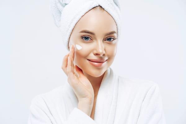 Saiba como se cuidar no inverno: mulher com uma toalha na cabeça passando creme no rosto.