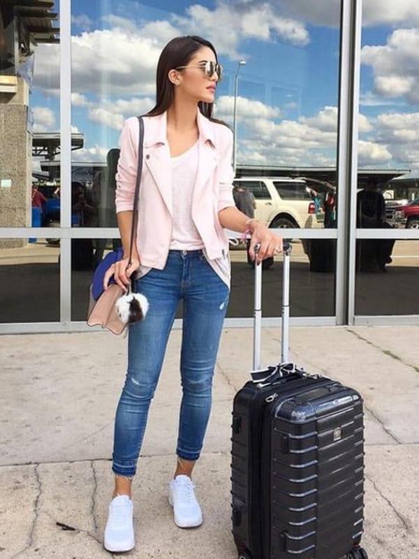 Como usar calça jeans: modelo usando calça jeans com mala de viagem aguardando táxi.