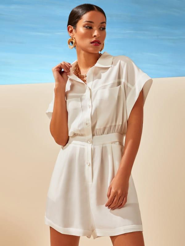 Como usar macaquinho: modelo vestindo um macaquinho off white com paisagem ao fundo.