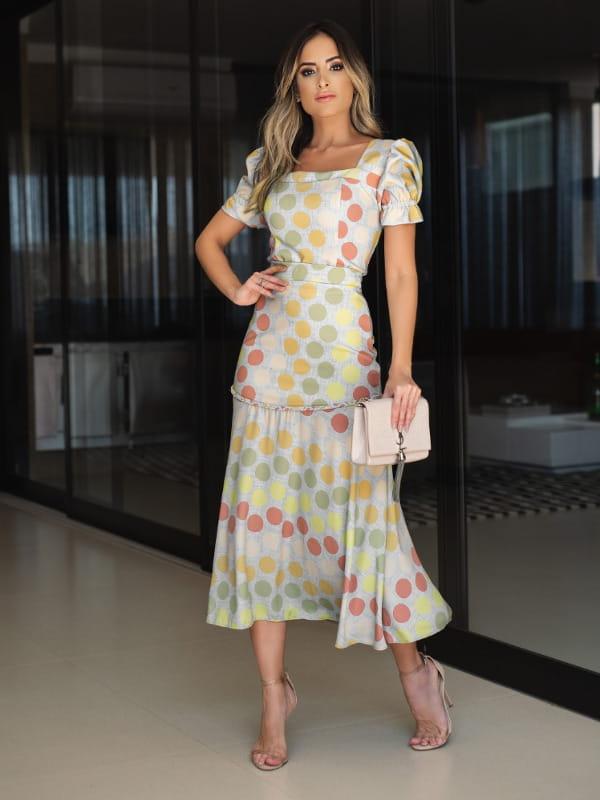 Como usar saia midi?: modelo vestindo saia midi forrada na pala e zíper lateral.