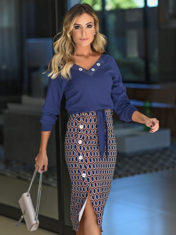 Como usar saia midi?: modelo vestindo saia midi estampada com abertura na lateral.