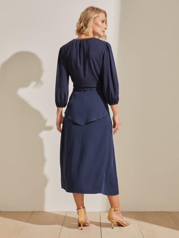 Como usar saia no inverno: modelo usando uma saia com blusa azul marinho mostrando as costas.