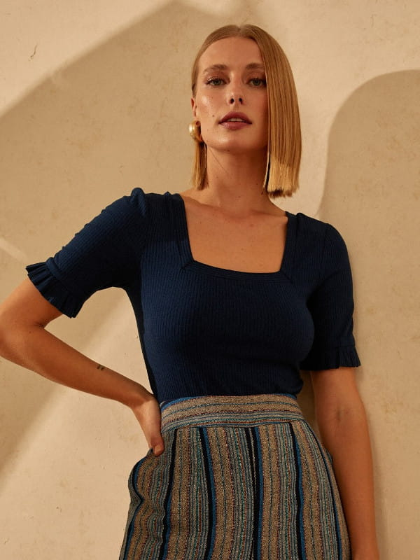 Decote quadrado: saiba como utilizá-lo: mulher vestindo uma blusa azul.