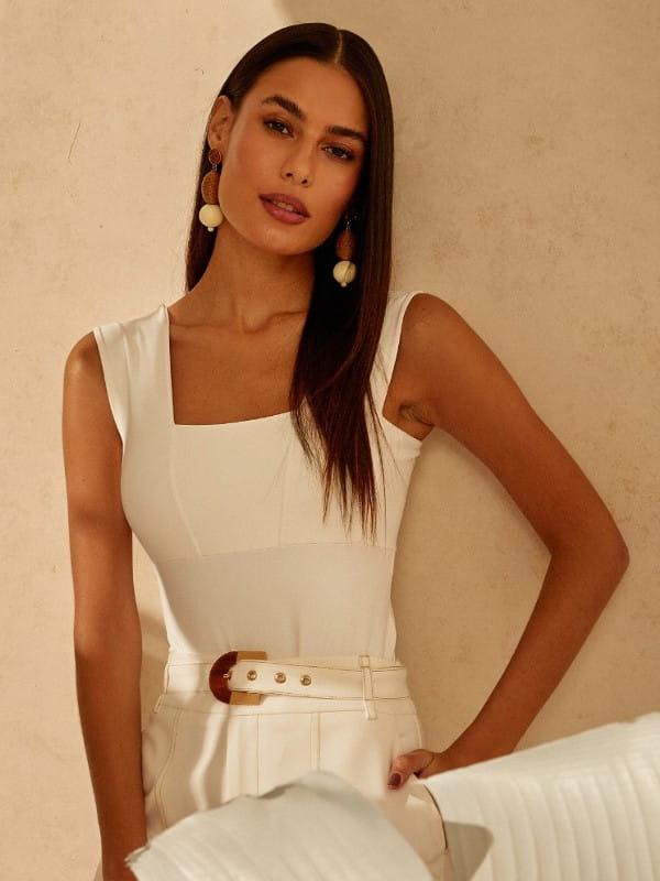 Decote quadrado: saiba como utilizá-lo: mulher encostada na parede com um look todo branco.