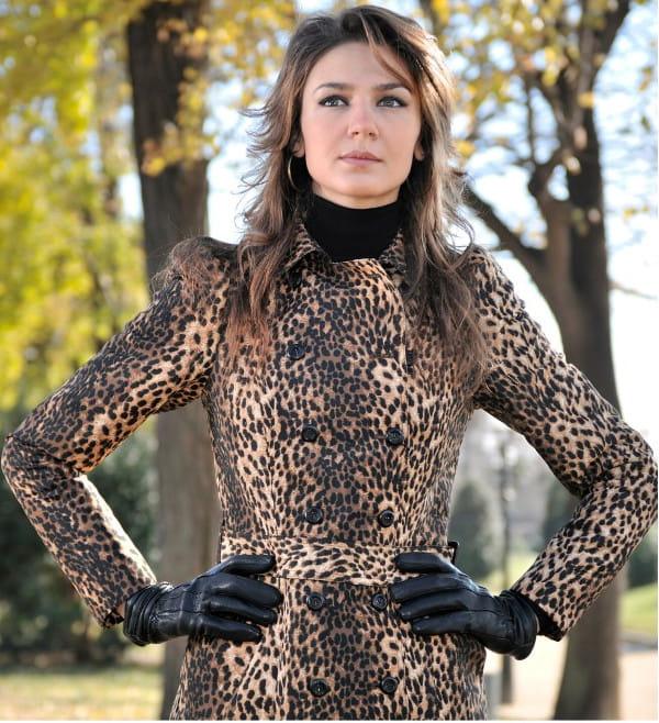 Estampas para o inverno 2020: modelo vestindo um casaco de oncinha com uma blusa preta por baixo.