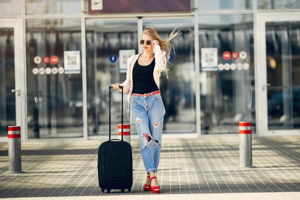 Lista de roupas para viagem: mulher no aeroporto aguardando um táxi.