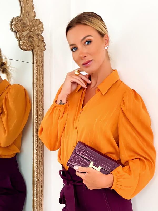 Look com camisa social feminina: modelo usando uma camisa social laranja.