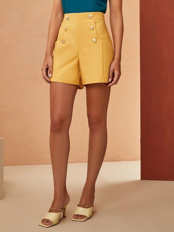Look com short alfaiataria: modelo vestindo short alfaiataria amarelo com botões.