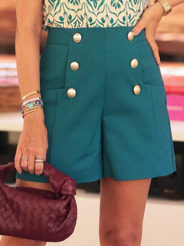 Look com short alfaiataria: modelo vestindo short alfaiataria com blusa estampada.