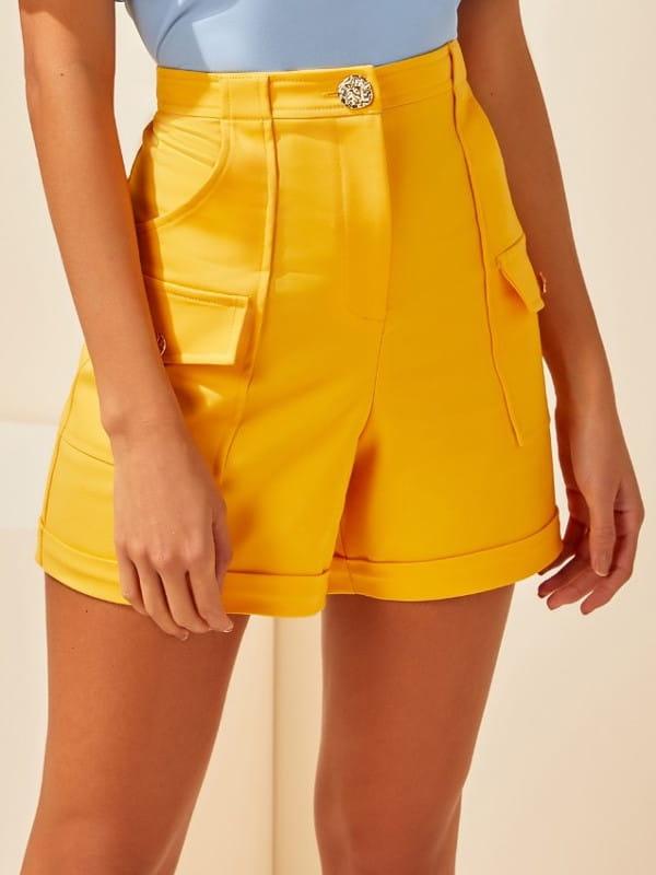 Look com short social: modelo vestindo um short mostarda com cintura alta.