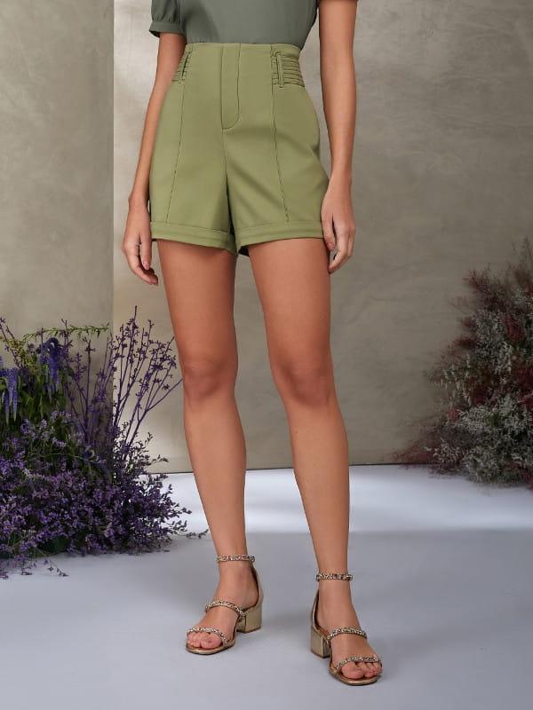 Look com short social: modelo vestindo um look monocromático verde.