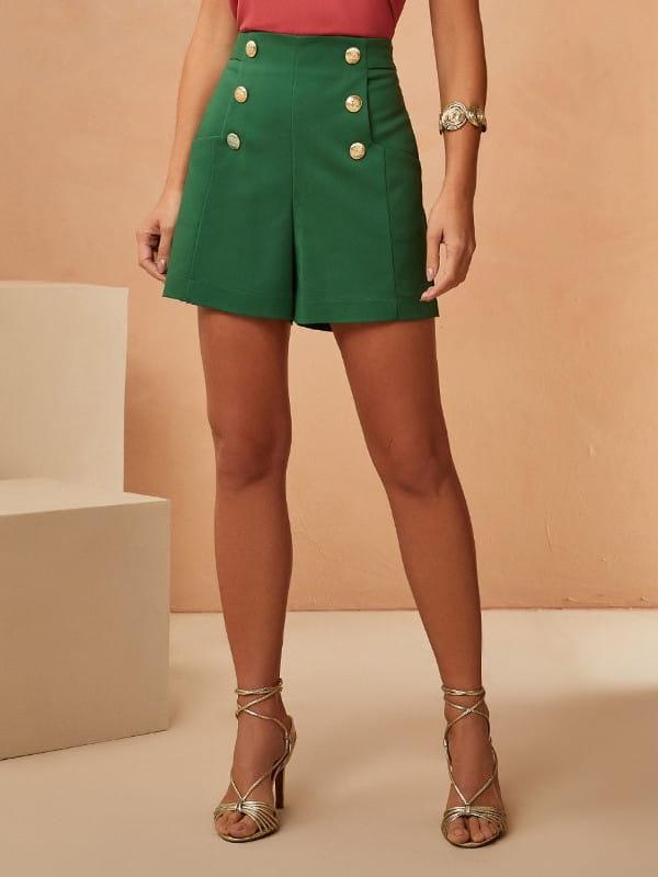 Look com short social: modelo vestindo um short verde com botões e blusa rosê.