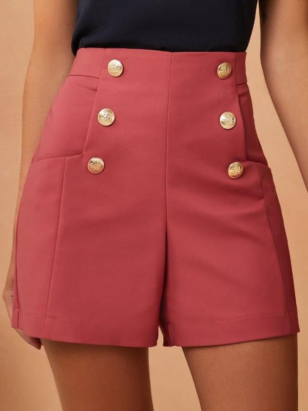Look com short social: modelo vestindo um short rosê com botões e blusa preta.