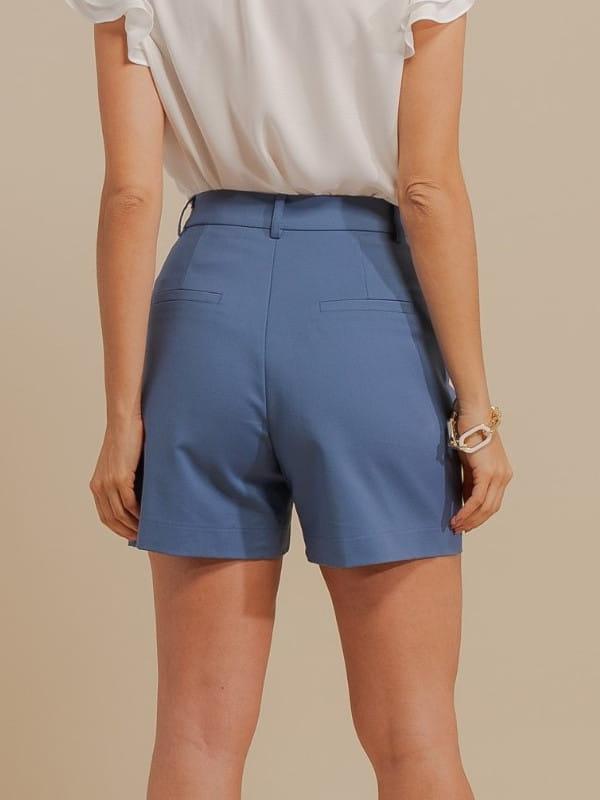 Inspire-se nos novos looks da semana: modelo vestindo shorts alfaiataria azul e blusa social - costas.