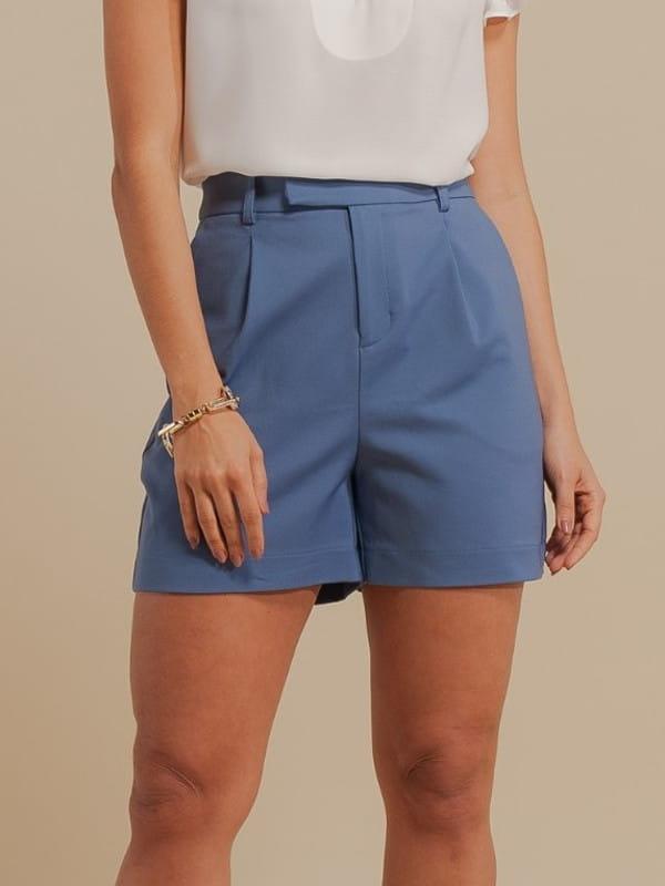 Look com short alfaiataria: modelo vestindo um short de alfaiataria cós transpassado - detalhe do produto.
