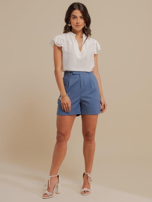Inspire-se nos novos looks da semana: modelo vestindo shorts alfaiataria azul e blusa social.