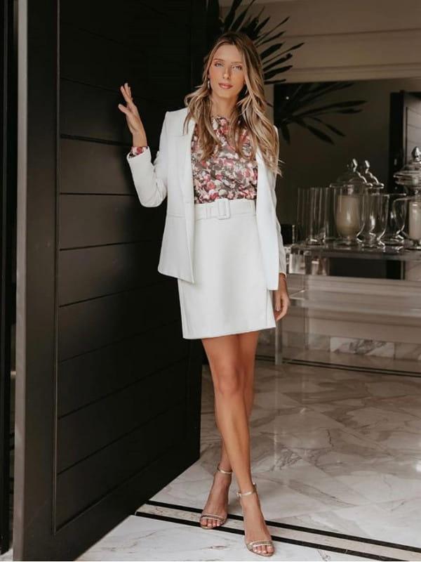 Look social feminino: modelo vestindo um blazer e saia brancos.