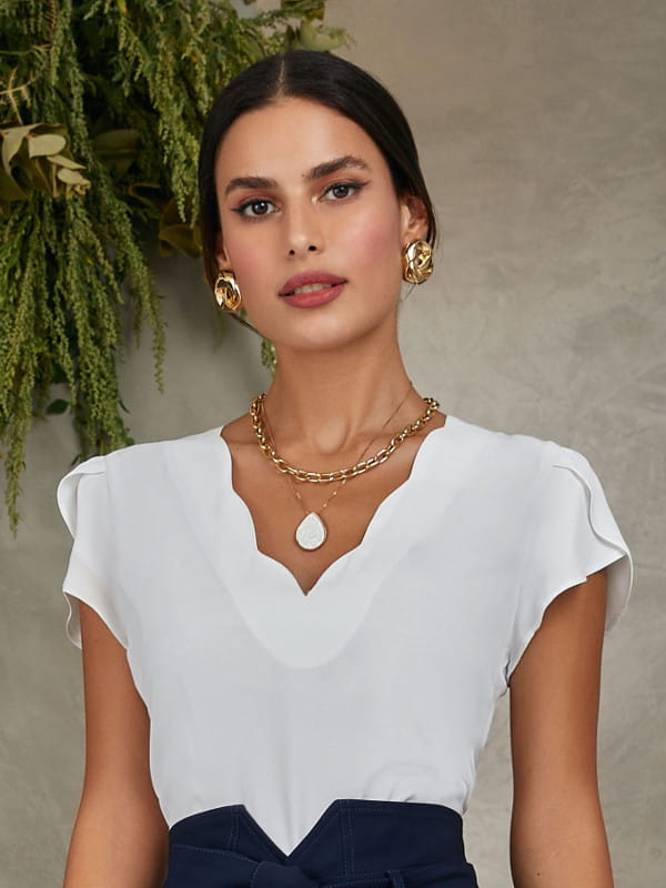 Look social feminino: modelo vestindo blusa branca de crepe com decote nuvem.