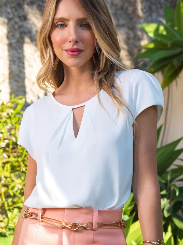 Look social feminino: modelo vestindo blusa branca de crepe com decote triângulo e pregas.