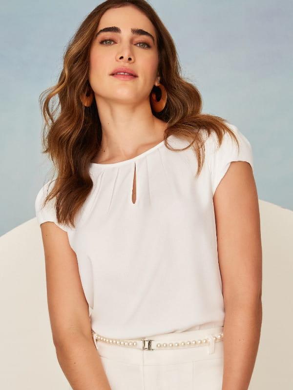 Look social feminino: modelo vestindo blusa branca de crepe com decote gota.