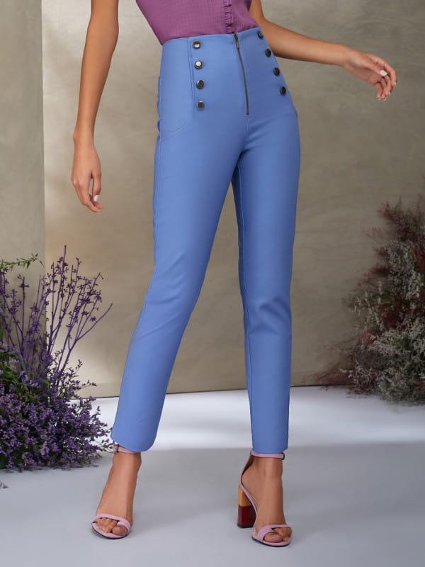 Look social feminino: modelo vestindo uma calça skinny azul com botões frontais.