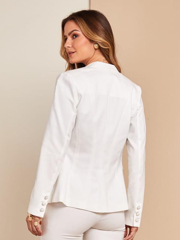 Looks com blazer branco feminino: mulher escolhendo modelos atrás de uma arara de roupas.