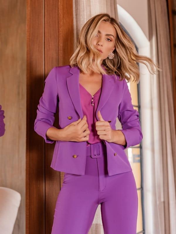 Looks com blazer feminino: modelo usando um blazer lilás com blusa decote V.