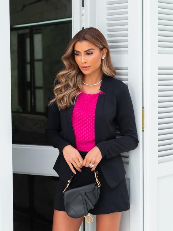Looks com blazer feminino: modelo usando um blazer preto com shorts.