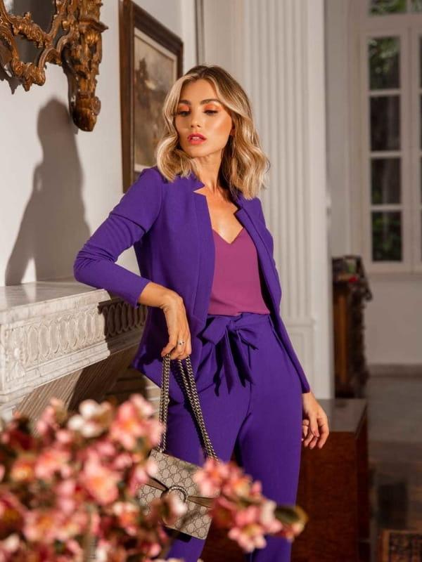 Looks com blazer feminino: modelo usando um blazer roxo com blusa decote V.