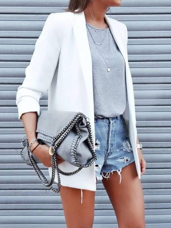 Looks com blazer feminino: modelo usando um blazer e shorts jeans rasgado.