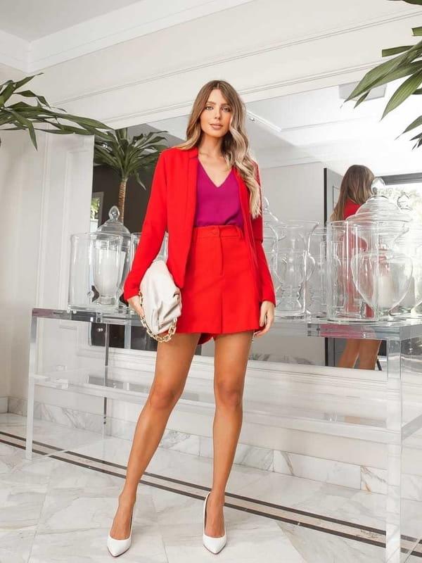 Looks com blazer feminino: modelo usando um blazer e shorts vermelhos.