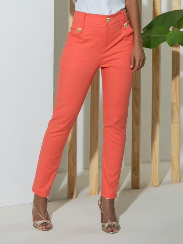 Looks com calça skinny: modelo vestindo uma calça laranja com botões nos bolsos.