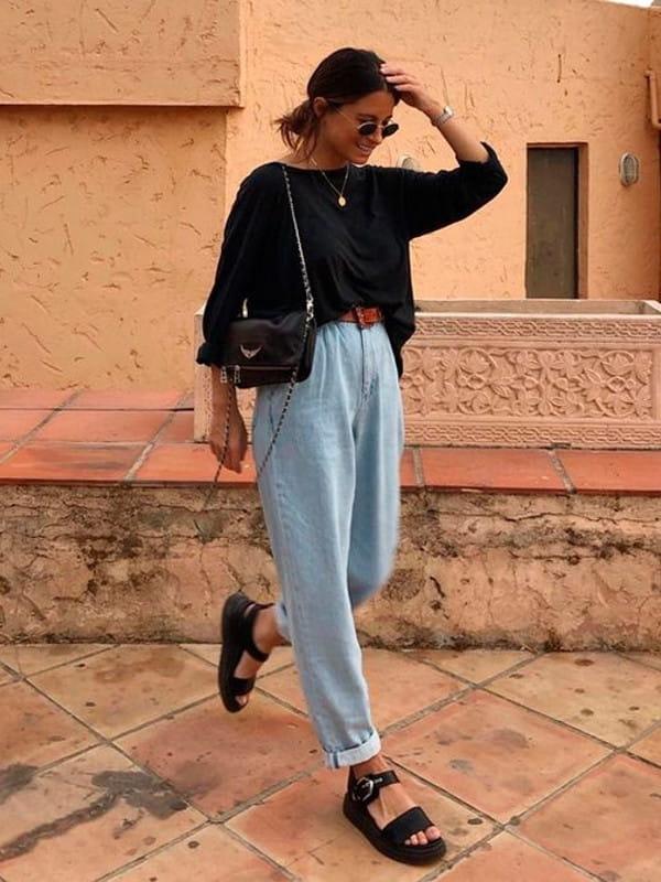 Looks com calça slouchy: modelo usando uma calça slouchy jeans com blusa preta.