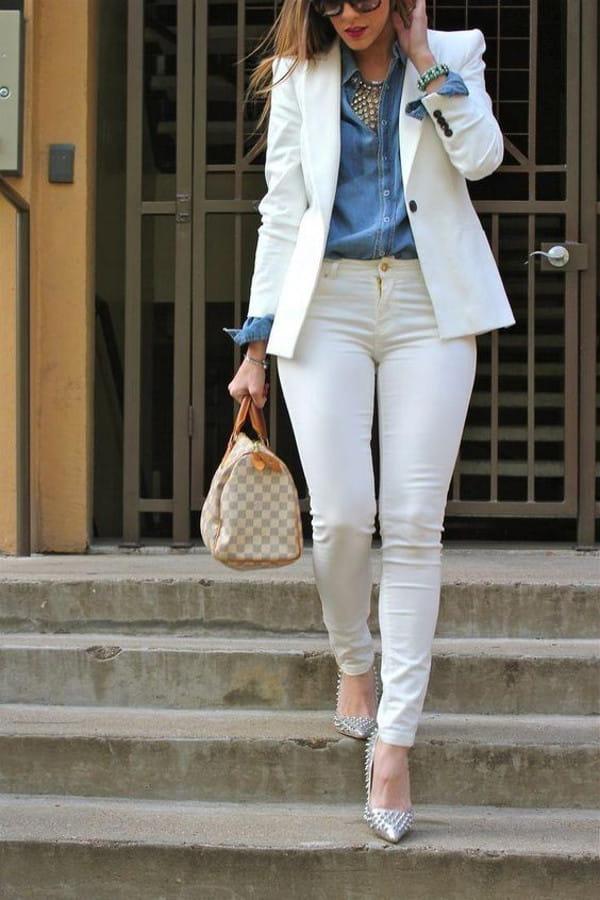 Looks com camisa jeans: mulher usando uma camisa jeans com blazer branco.