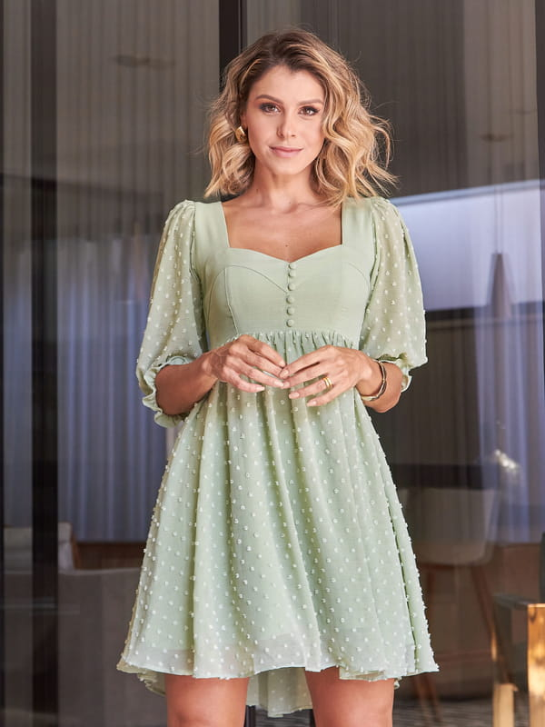 Looks com vestidos: modelo com um vestido estilo evasê.