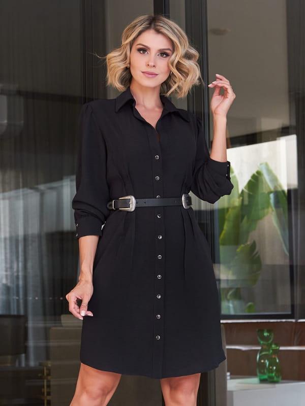 Looks com vestidos: modelo com um vestido preto e botões em toda a frente.