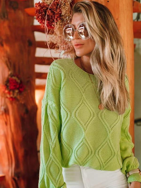 Looks de inverno para trabalhar: modelo vestindo uma blusa de tricot na cor verde claro.