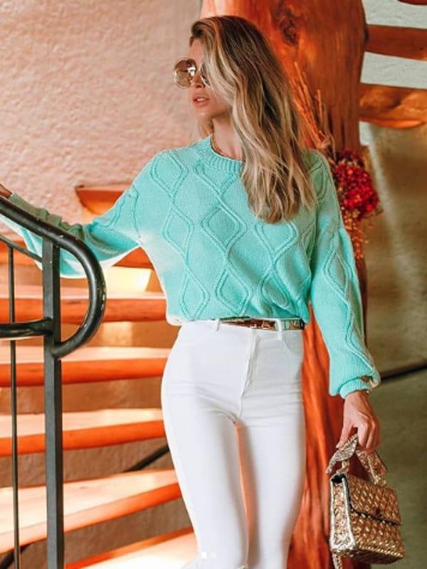 Looks de inverno para trabalhar: modelo vestindo uma blusa de tricot verde água.