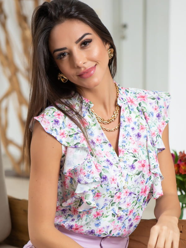 Looks femininos para o verão 2021: modelo usando uma blusa de crepe floral com babados.