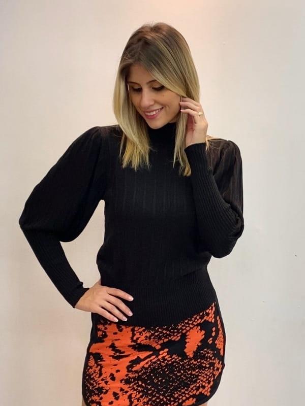 Looks para ficar em casa sem perder o estilo: mulher com blusa de tricot.