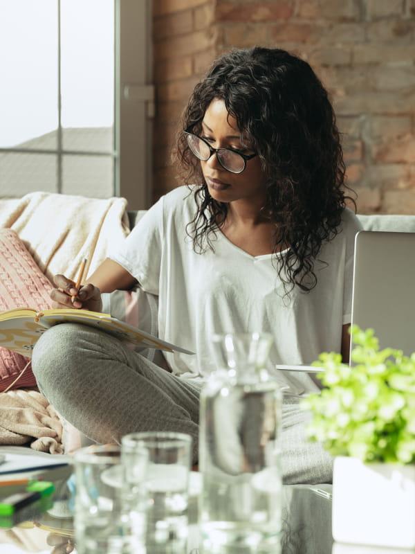 Looks para ficar em casa sem perder o estilo: mulher trabalhando no sofá com seu notebook.