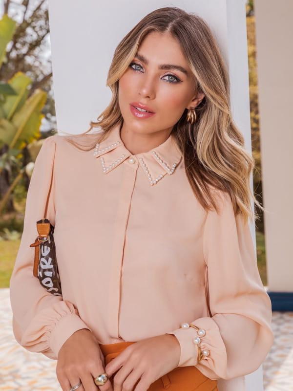Looks volumosos: saiba como usar: modelo vestindo uma camisa de crepe com pérolas na gola.