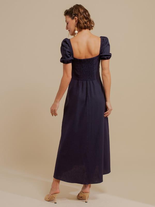 Looks volumosos: saiba como usar: modelo mostrando as costas de um vestido de linho azul marinho.