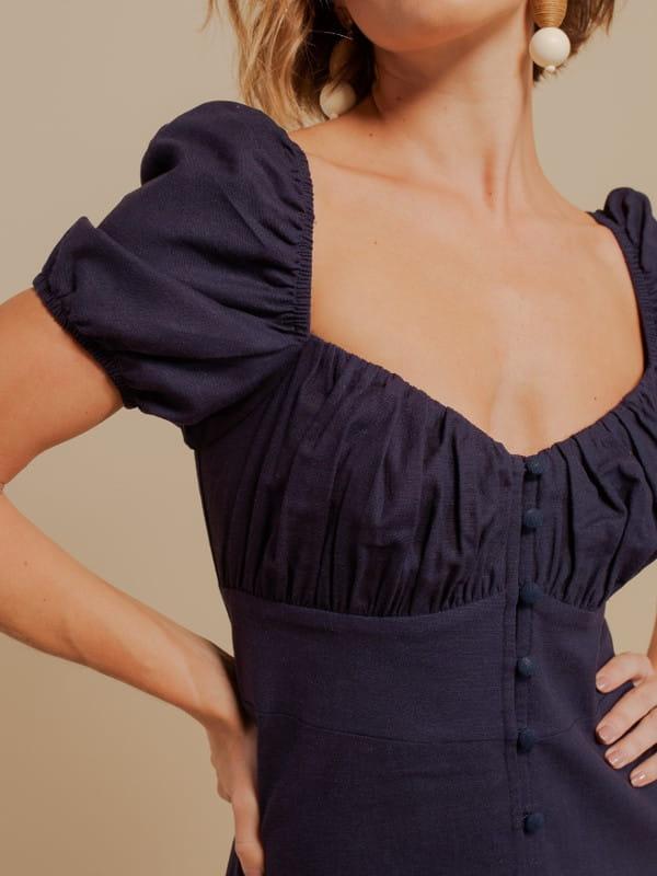 Looks volumosos: saiba como usar: mulher com um vestido com mangas bufantes azul marinho - detalhe do decote.