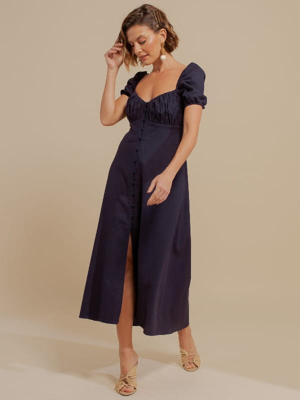 Looks volumosos: saiba como usar: modelo com um vestido de linho azul marinho.