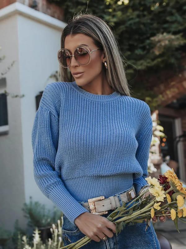 Moda Outono Inverno 2021: modelo vestindo uma blusa de tricot azul com prega na manga.