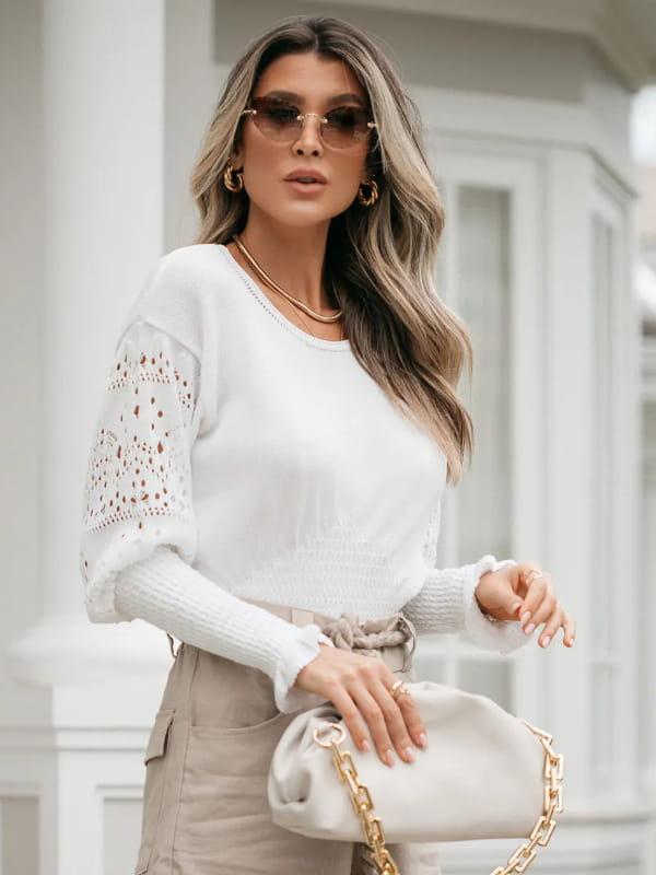 Moda Outono Inverno 2021: modelo vestindo uma blusa de tricot com manga rendada branca.