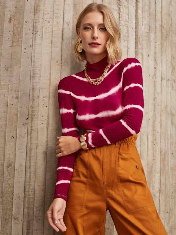Moda Tie Dye: conheça a origem dessa tendência: modelo com uma blusa de malha tie dye vinho.